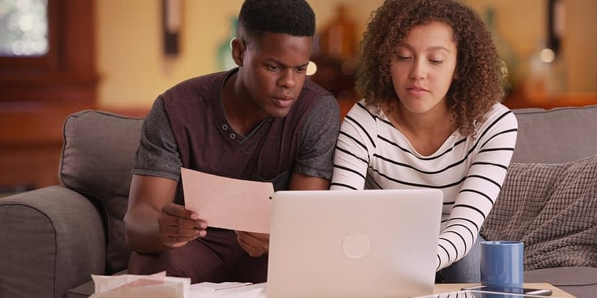 young couple working on documents on laptop